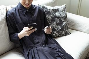 スマートフォンでオンラインショッピングをする女性の写真素材 [FYI04607335]
