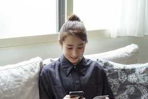 スマートフォンでオンラインショッピングをする女性の写真素材 [FYI04607338]