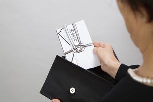 バッグから香典を出す女性の写真素材 [FYI04607438]