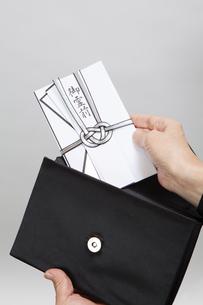 バッグから香典を出す女性の写真素材 [FYI04607439]