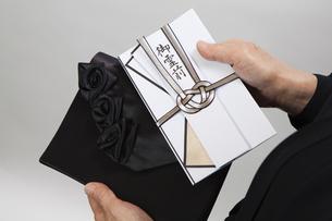 バッグから香典を出す女性の写真素材 [FYI04607440]