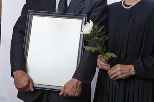遺影を持つ喪主と菊の花を持つ女性の写真素材 [FYI04607443]