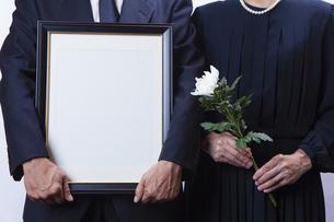 遺影を持つ喪主と菊の花を持つ女性の写真素材 [FYI04607444]