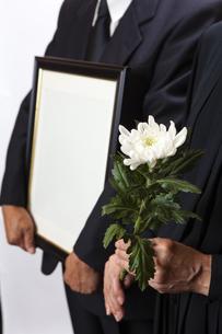 遺影を持つ喪主と菊の花を持つ女性の写真素材 [FYI04607445]