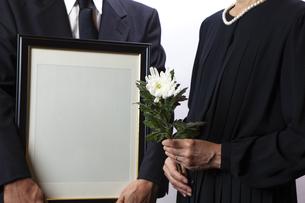 遺影を持つ喪主と菊の花を持つ女性の写真素材 [FYI04607446]