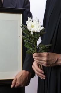 遺影を持つ喪主と菊の花を持つ女性の写真素材 [FYI04607447]