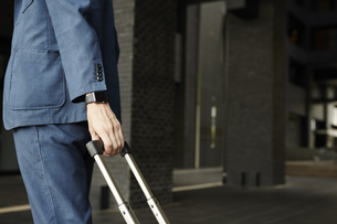 スマートウォッチとスーツケースを引っ張るビジネスマンの写真素材 [FYI04607691]