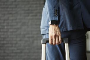 スマートウォッチとスーツケースを引っ張るビジネスマンの写真素材 [FYI04607693]