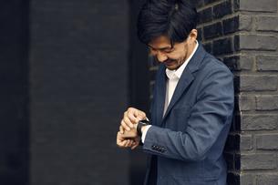 スマートウォッチを触るビジネスマンの写真素材 [FYI04607700]
