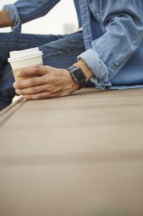 コーヒーを飲むスマートウォッチをした男性の写真素材 [FYI04607712]