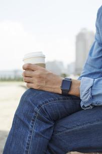 コーヒーを飲むスマートウォッチをした男性の写真素材 [FYI04607719]