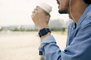 コーヒーを飲むスマートウォッチをした男性の写真素材 [FYI04607728]