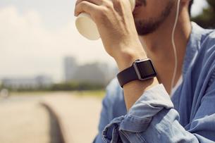 コーヒーを飲むスマートウォッチをした男性の写真素材 [FYI04607732]