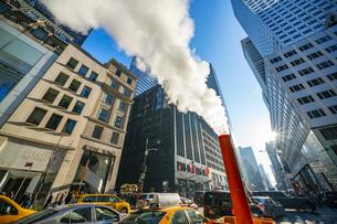 クリスマスホリデーシーズンのミッドタウン五番街高層ビル群の間を漂う蒸気。冬の太陽に照らされ漂う蒸気の中を交通と人々が行き交いますの写真素材 [FYI04607950]