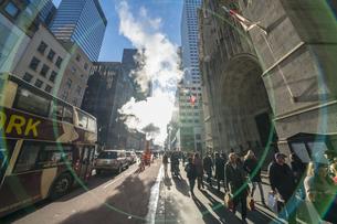 クリスマスホリデーシーズンのミッドタウン五番街高層ビル群の間を漂う蒸気。冬の太陽に照らされ漂う蒸気の中を交通と人々が行き交いますの写真素材 [FYI04607955]
