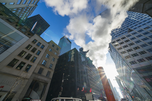 クリスマスホリデーシーズンのミッドタウン五番街高層ビル群の間を漂う蒸気。冬の太陽に照らされ漂う蒸気の中を交通と人々が行き交いますの写真素材 [FYI04607959]