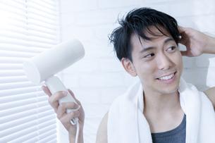 ドライヤーで髪を乾かす男性の写真素材 [FYI04608031]