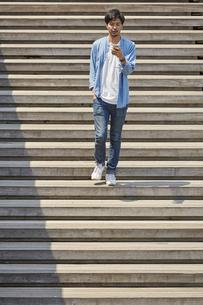 スマートフォンを見ながら階段を下りる男性の写真素材 [FYI04608145]