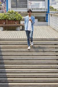 スマートフォンを見ながら階段を下りる男性の写真素材 [FYI04608147]