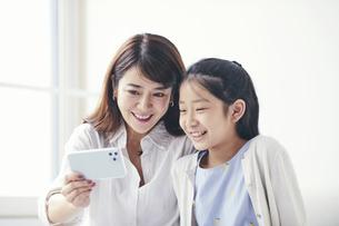 ソファに座りスマートフォンを持つ母親と女の子の写真素材 [FYI04608245]
