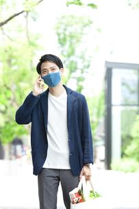マスクをして電話する男性の写真素材 [FYI04608375]
