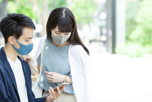 マスクをしてスマートフォンを見る男性と女性の写真素材 [FYI04608414]