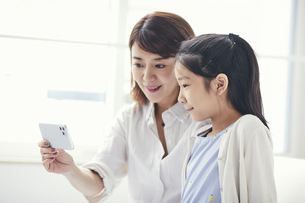 ソファに座りスマートフォンを持つ母親と女の子の写真素材 [FYI04608477]