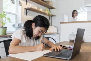 オンライン授業を受ける女の子と家事をする母の写真素材 [FYI04608993]