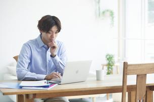 ノートパソコンを見る若い男性 の写真素材 [FYI04609766]