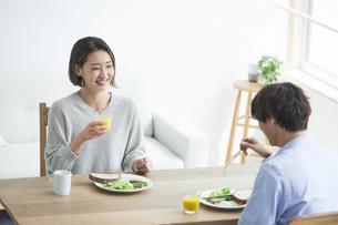 リビングで食事をする若い男性と女性の写真素材 [FYI04609778]