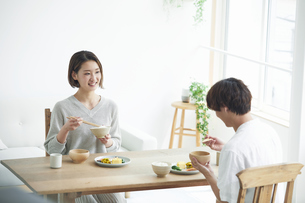 リビングで食事をする若い男性と女性の写真素材 [FYI04609806]