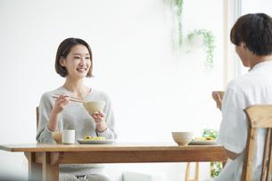 リビングで食事をする若い男性と女性の写真素材 [FYI04609809]