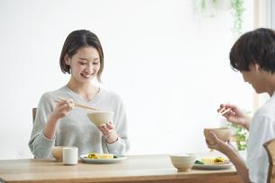 リビングで食事をする若い男性と女性の写真素材 [FYI04609810]