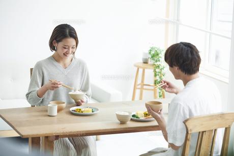 リビングで食事をする若い男性と女性の写真素材 [FYI04609811]