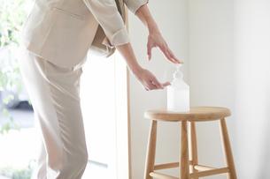 玄関でアルコールで除菌をする若い女性の写真素材 [FYI04609812]
