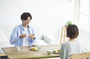 リビングで食事をする若い男性と女性の写真素材 [FYI04609815]