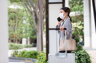 バス停でスーツケースを持ってバスを待つ女性の写真素材 [FYI04609866]