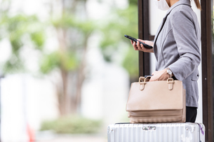 バス停でスーツケースを持ってバスを待つ女性の写真素材 [FYI04609867]