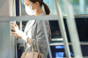 マスク姿で電車通勤をする女性の写真素材 [FYI04609940]