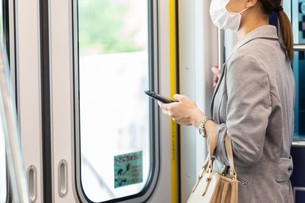 マスク姿で電車通勤をする女性の写真素材 [FYI04609941]
