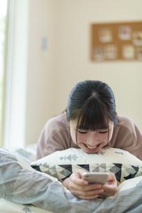 ベットに寝そべりスマホを見る女子の写真素材 [FYI04610674]