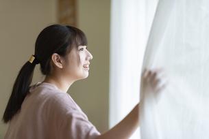 カーテンを開けて外を見る女性の写真素材 [FYI04610718]