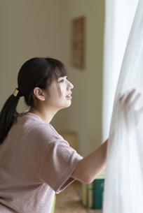カーテンを開けて外を見る女性の写真素材 [FYI04610719]