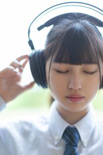 ヘッドホンで音楽を聴く女子学生の写真素材 [FYI04610765]