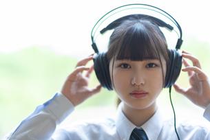 ヘッドホンで音楽を聴く女子学生の写真素材 [FYI04610767]