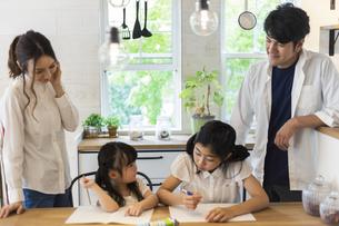 勉強をする姉妹と見守る両親の写真素材 [FYI04611751]