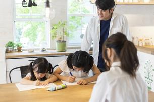 勉強をする姉妹と見守る両親の写真素材 [FYI04611754]