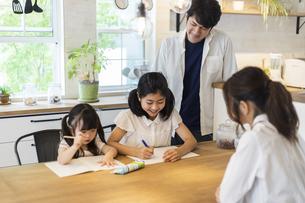 勉強をする姉妹と見守る両親の写真素材 [FYI04611756]