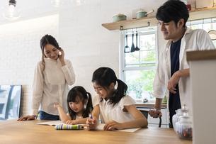 勉強をする姉妹と見守る両親の写真素材 [FYI04611758]