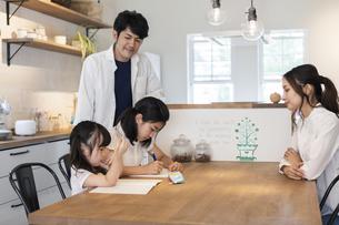 勉強をする姉妹と見守る両親の写真素材 [FYI04611759]